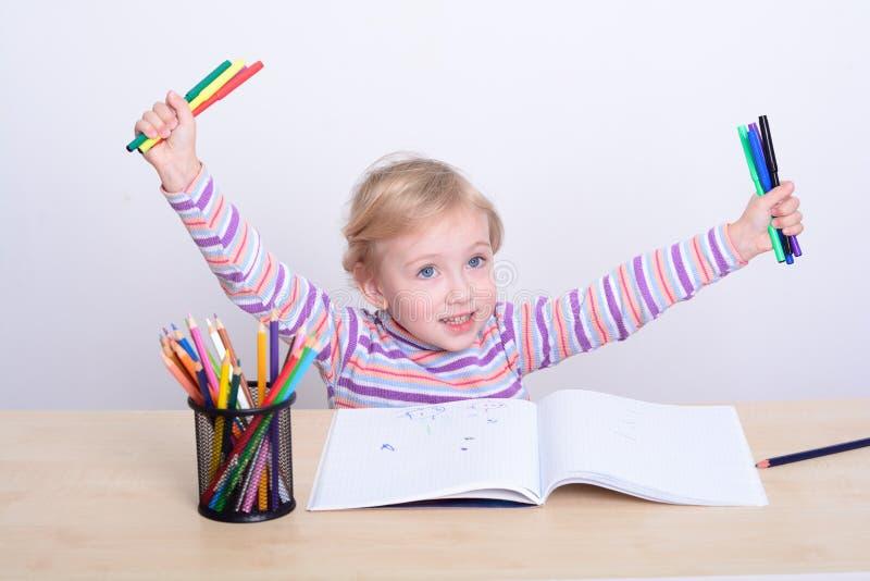 Σχέδιο κοριτσιών με τα ζωηρόχρωμα μολύβια στοκ φωτογραφία