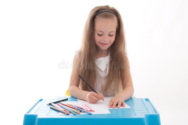 Σχέδιο μικρών κοριτσιών που χρησιμοποιεί τα μολύβια χρώματος που απομονώνονται στο λευκό στοκ εικόνες