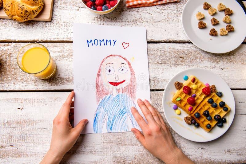 Σχέδιο Childs του mom της το λουλούδι ημέρας δίνει το γιο μητέρων mum Γεύμα προγευμάτων στοκ φωτογραφίες