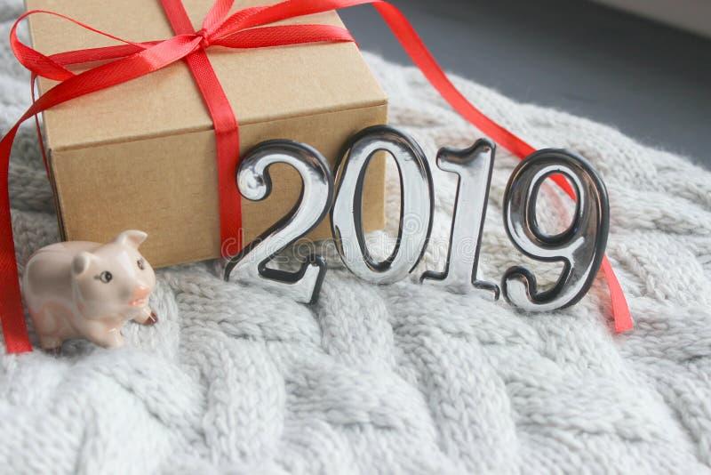 Σχήματα 2019, νέες διακοπές έτους, συγχαρητήρια Νέο υπόβαθρο έτους, αριθμοί, σύμβολο, ο χοίρος και το δώρο με μια κόκκινη κορδέλλ στοκ εικόνα