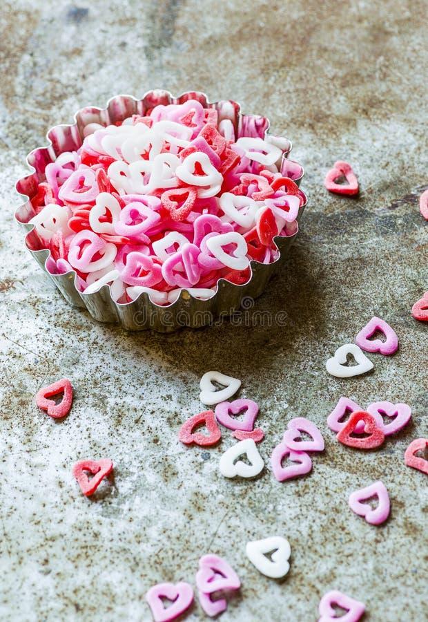 Σχήματα ροζ καρδιακού σακχάρου στο ριζικό φόντο στοκ φωτογραφία