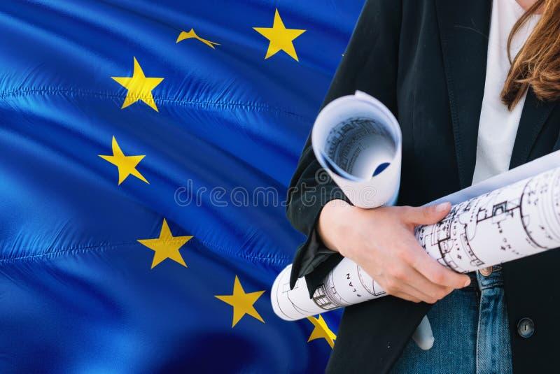 Σχεδιάγραμμα εκμετάλλευσης γυναικών αρχιτεκτόνων στο κυματίζοντας κλίμα σημαιών της Ευρωπαϊκής Ένωσης Έννοια κατασκευής και αρχιτ στοκ εικόνα