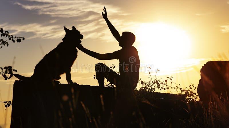 Σχεδιάγραμμα σκιαγραφιών του ατόμου και του σκυλιού ενάντια στον ορίζοντα του νεφελώδους ουρανού, γερμανική συνεδρίαση ποιμένων τ στοκ εικόνα