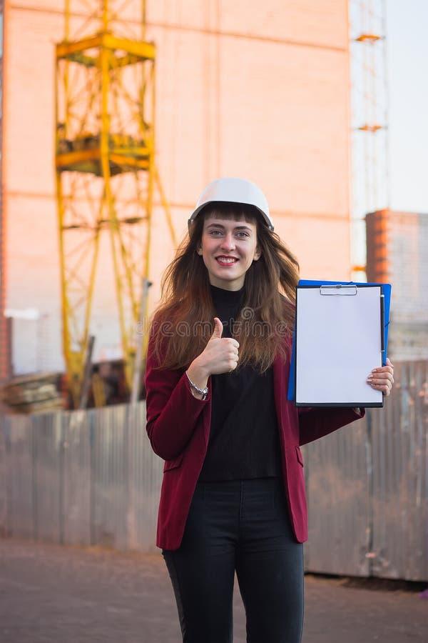 Σχεδιαγράμματα εκμετάλλευσης γυναικών, περιοχή αποκομμάτων Χαμογελώντας αρχιτέκτονας στο κράνος στην οικοδόμηση στοκ φωτογραφίες