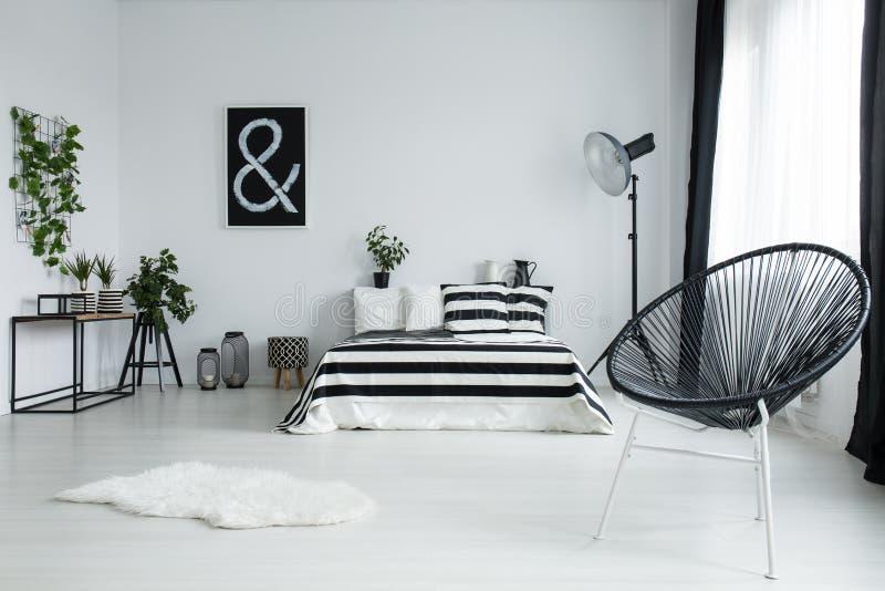 Σχεδιασμένη μαύρη καρέκλα στη σύγχρονη κρεβατοκάμαρα στοκ εικόνες