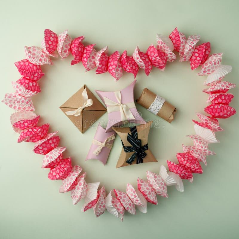 Σχεδιασμένος με μορφή ενός cupcake με μορφή των κιβωτίων καρδιών και δώρων σε ένα πράσινο υπόβαθρο κρητιδογραφιών, διάστημα αντιγ στοκ εικόνες