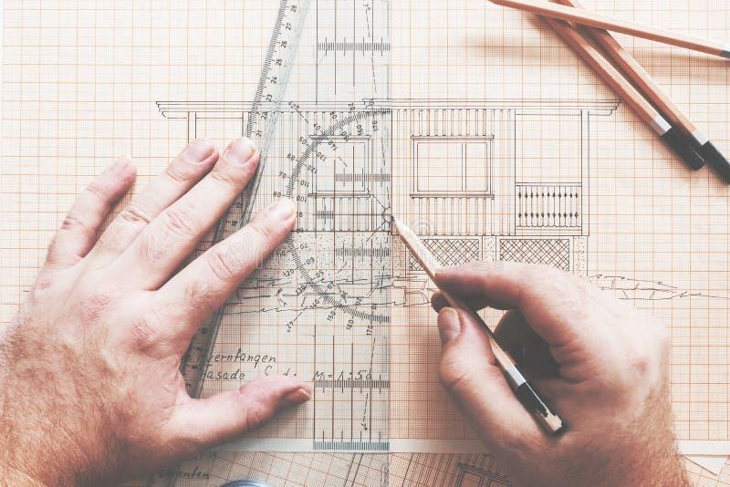 Σχεδιαστής/αρχιτέκτονας που επισύρει την προσοχή μια καμπίνα στο drawingboard στοκ εικόνες