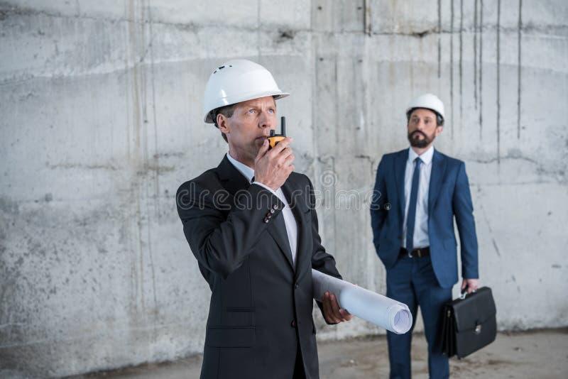 Σχεδιάγραμμα εκμετάλλευσης αρχιτεκτόνων και χρησιμοποίηση walkie-talkie ενώ συνάδελφος με το χαρτοφύλακα που στέκεται πίσω στοκ εικόνες