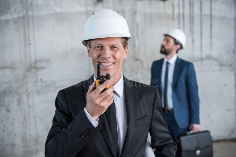 Σχεδιάγραμμα εκμετάλλευσης αρχιτεκτόνων και χρησιμοποίηση walkie-talkie ενώ συνάδελφος με το χαρτοφύλακα που στέκεται πίσω στοκ εικόνα