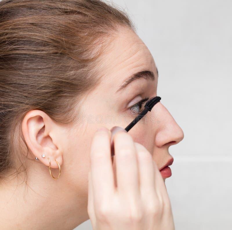 Σχεδιάγραμμα κινηματογραφήσεων σε πρώτο πλάνο της νέας γυναίκας που εφαρμόζει mascara στα eyelashes της στοκ εικόνες