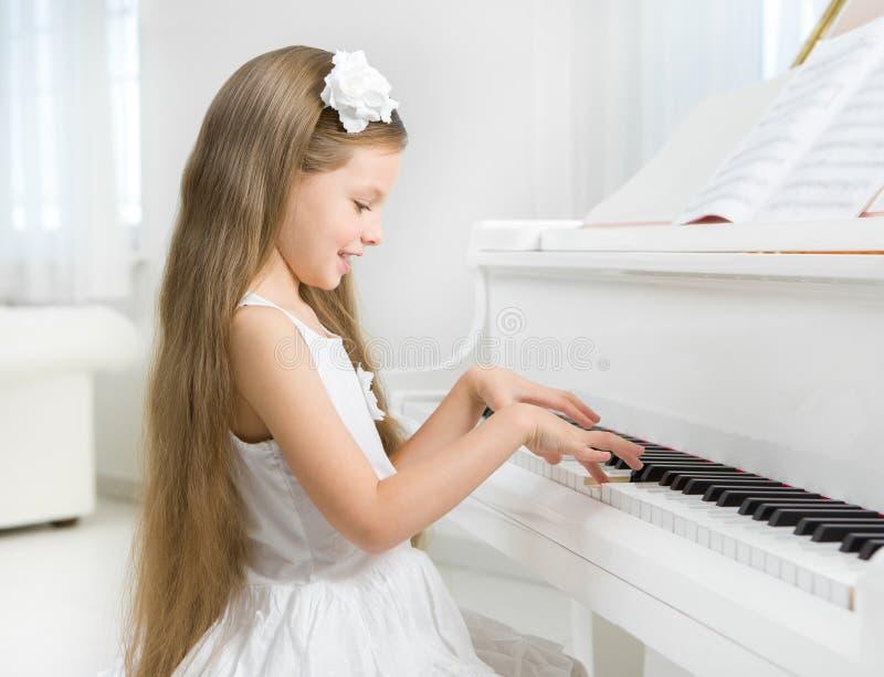 Σχεδιάγραμμα του μικρού κοριτσιού στο άσπρο πιάνο παιχνιδιού φορεμάτων στοκ φωτογραφία με δικαίωμα ελεύθερης χρήσης