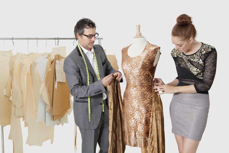 Σχεδιαστές μόδας που εργάζονται μαζί σε μια εξάρτηση στο στούντιο σχεδίου στοκ φωτογραφία με δικαίωμα ελεύθερης χρήσης