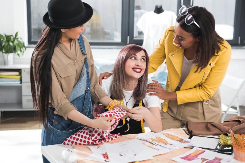 Σχεδιαστές μόδας που εργάζονται μαζί στο πρόγραμμα στο κατάστημα ιματισμού στοκ φωτογραφία με δικαίωμα ελεύθερης χρήσης