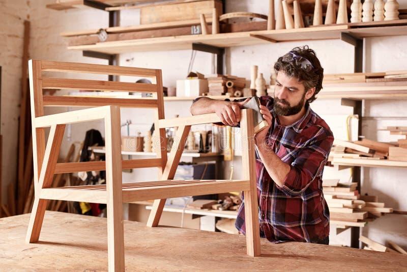 Σχεδιαστής επίπλων που στρώνει με άμμο ένα ξύλινο πλαίσιο καρεκλών στοκ εικόνες