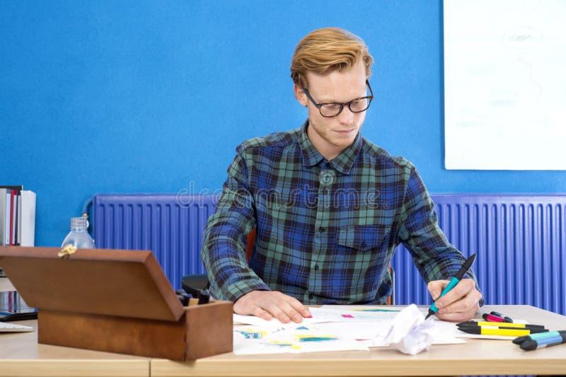 Σχεδιαστής που καθιστά το σκίτσο στην αρχή στοκ φωτογραφία