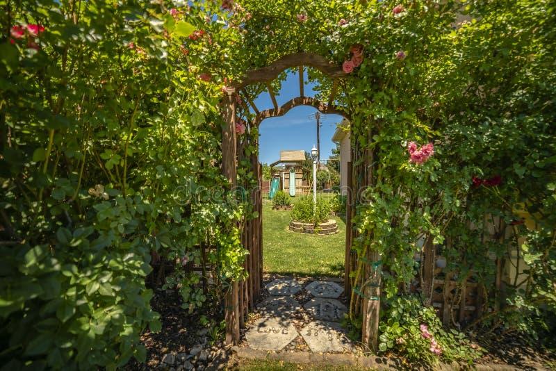 Σχηματισμένος αψίδα ξύλινος άξονας στην είσοδο ενός κήπου με τις φωτογραφικές διαφάνειες και την ταλάντευση θεάτρων στοκ εικόνες με δικαίωμα ελεύθερης χρήσης