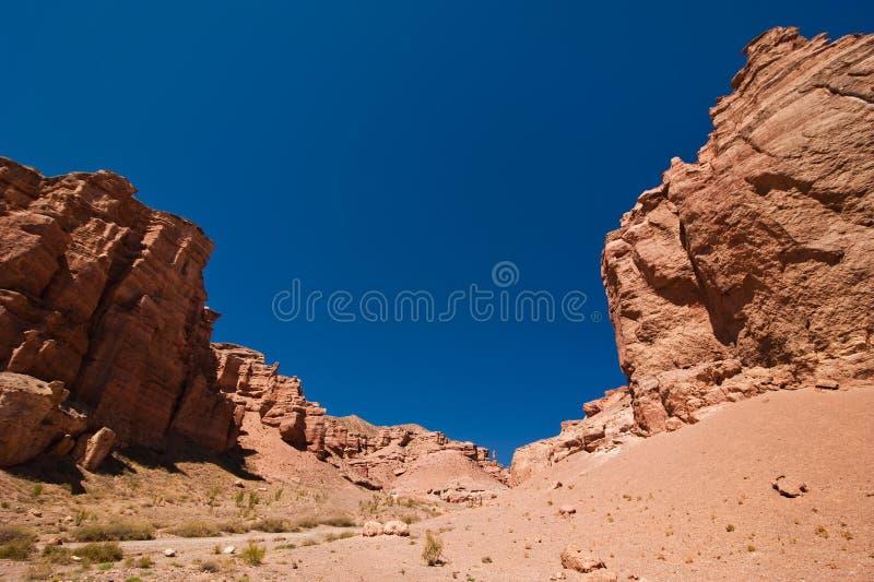 Σχηματισμοί βράχου στο φαράγγι Charyn κάτω από το μπλε ουρανό στοκ εικόνες