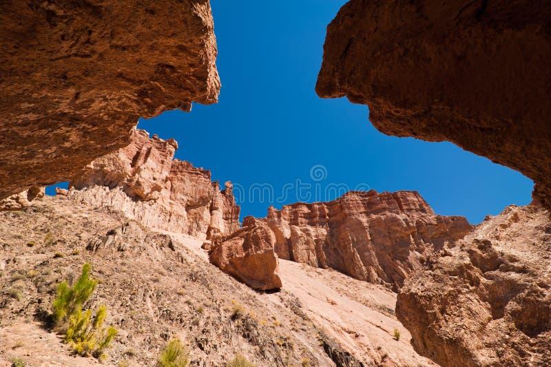 Σχηματισμοί βράχου στο φαράγγι Charyn κάτω από το μπλε ουρανό στοκ εικόνα