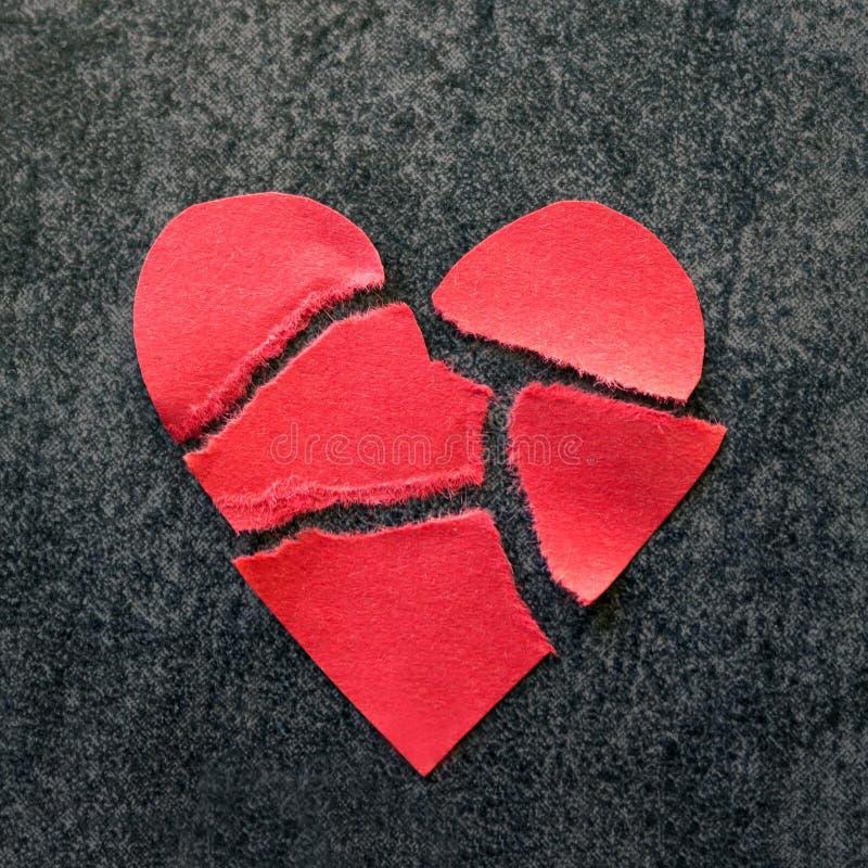 Σχισμένη κόκκινη καρδιά εγγράφου Μαύρη ανασκόπηση Η έννοια του διαζυγίου, στοκ εικόνες