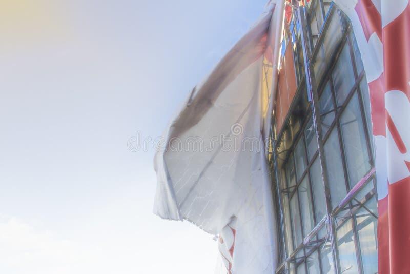 Σχισμένος πίνακας διαφημίσεων που αναπτύσσεται στον αέρα ενάντια στο μπλε ουρανό στοκ εικόνες