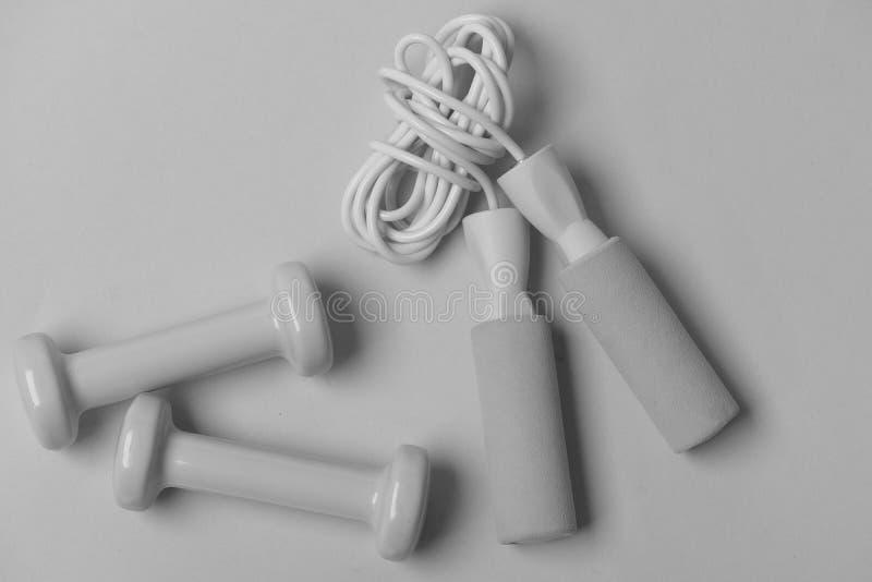 Σχοινί άλματος και barbells τοποθετημένος το ένα δίπλα στο άλλο στοκ φωτογραφία