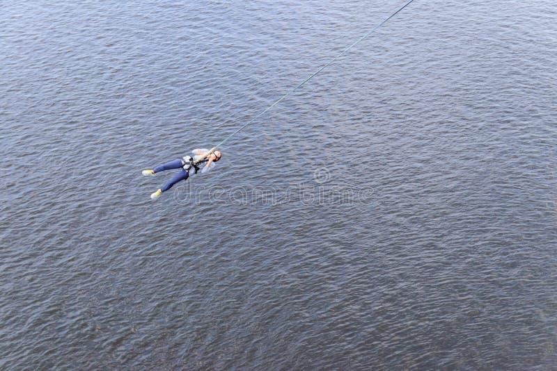Σχοινί που πηδά από το μεγάλο υψόμετρο της γέφυρας Bungee που πηδά από τη για τους πεζούς γέφυρα πέρα από τον όμορφο ποταμό στοκ εικόνες