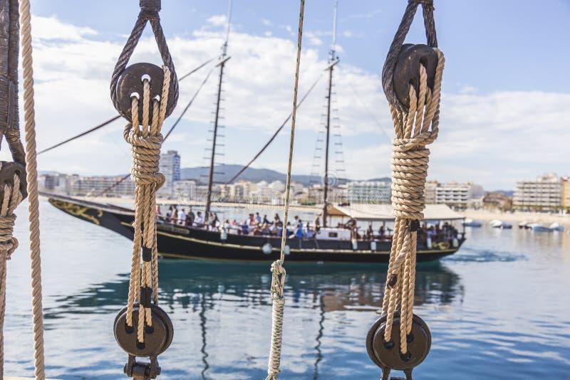 Σχοινί σκαφών και μια όμορφη πλέοντας βάρκα στο υπόβαθρο στοκ εικόνα