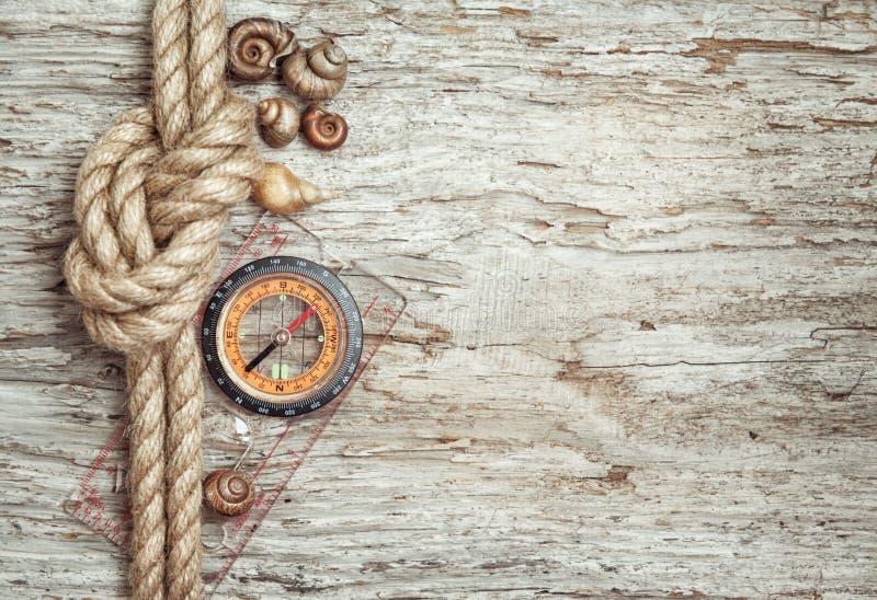 Σχοινί σκαφών, κοχύλια, πυξίδα και ξύλινο υπόβαθρο στοκ εικόνα