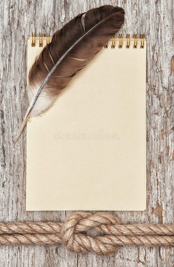 Σχοινί σκαφών, φτερό, σπειροειδές σημειωματάριο και ξύλινο υπόβαθρο στοκ φωτογραφία με δικαίωμα ελεύθερης χρήσης