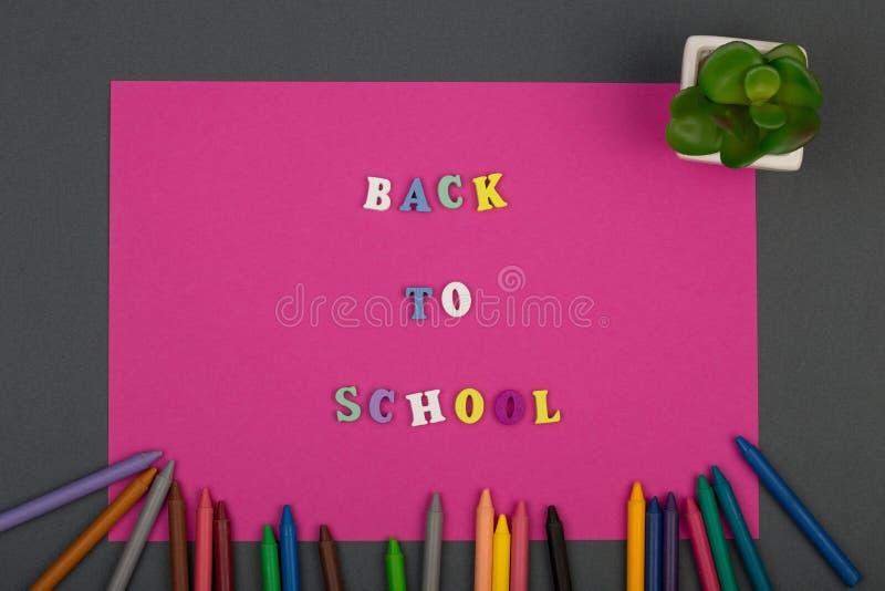 Σχολείο που τίθεται με το ρόδινα έγγραφο, το κείμενο & x22 Πίσω στο school& x22  από τις ξύλινα επιστολές και τα κραγιόνια στοκ φωτογραφία