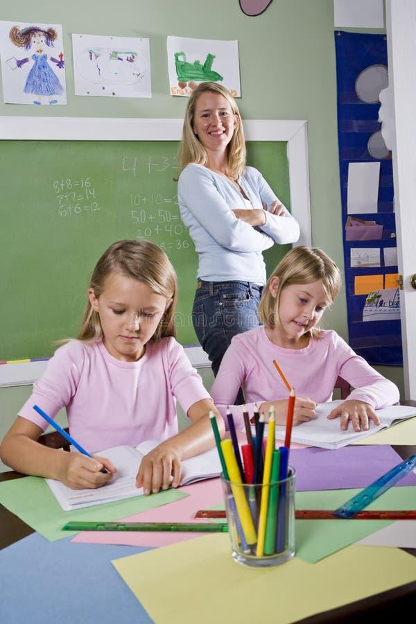Σχολικά κορίτσια που γράφουν στα σημειωματάρια με το δάσκαλο στοκ εικόνα