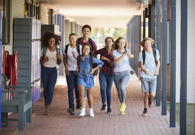 Σχολικά παιδιά εφήβων που τρέχουν στο διάδρομο γυμνασίου στοκ εικόνες