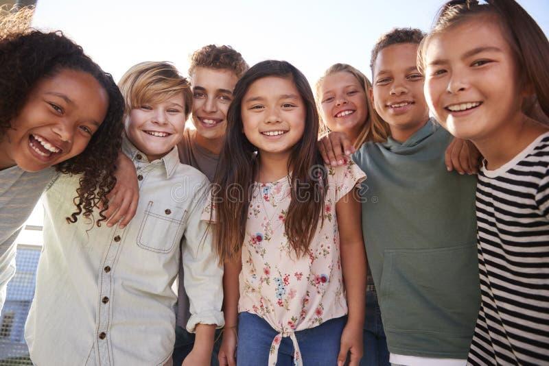 Σχολικά παιδιά που κρεμούν έξω κατά τη διάρκεια του σπασίματος, που χαμογελά στη κάμερα στοκ φωτογραφίες