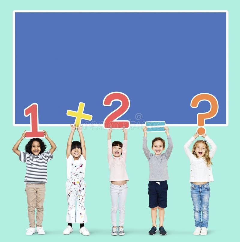 Σχολικά παιδιά που μαθαίνουν τα μαθηματικά με τους αριθμούς στοκ εικόνα