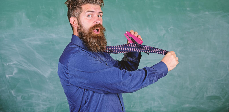 Σχολικά χαρτικά Stapler χρήσης ατόμων ατημέλητος επικίνδυνος τρόπος Η επίσημη γραβάτα ένδυσης δασκάλων Hipster κρατά stapler δάσκ στοκ εικόνα με δικαίωμα ελεύθερης χρήσης