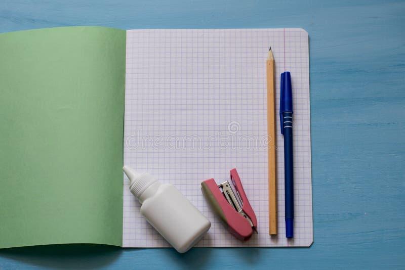Σχολικές προμήθειες σε ένα φύλλο σημειωματάριων Σχολική έννοια με τα χαρτικά Σχολικοί σημειωματάριο, κόλλα, stapler, μολύβι και σ στοκ φωτογραφίες