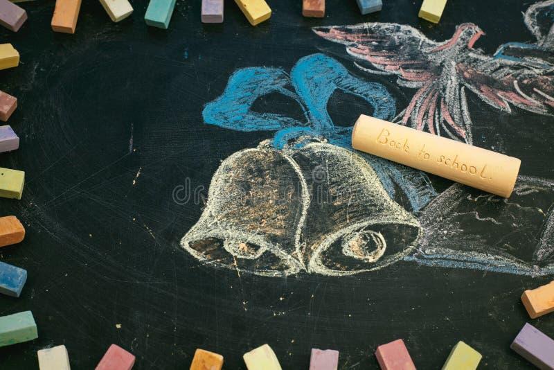 Σχολική έννοια στα συρμένα κουδούνια και το σημειωματάριο κιμωλίας πινάκων στοκ φωτογραφία