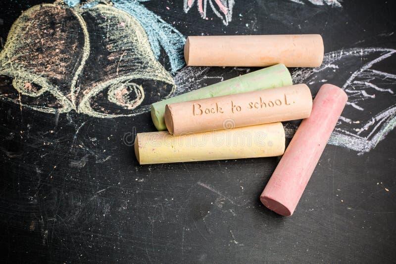 Σχολική έννοια στα συρμένα κουδούνια και το σημειωματάριο κιμωλίας πινάκων στοκ εικόνες