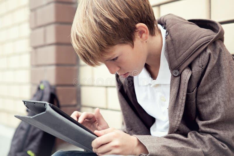 Σχολικός έφηβος με την ηλεκτρονική συνεδρίαση ταμπλετών στοκ φωτογραφίες