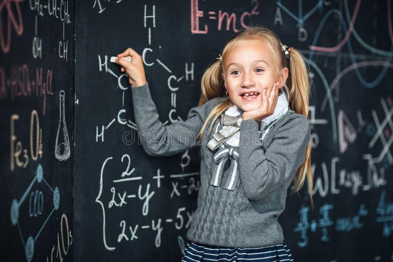 Σχολικός πίνακας, math τύπος, μαθήτρια με το πολύ έκπληκτο πρόσωπο στοκ φωτογραφία