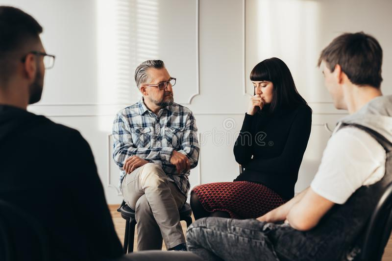 Σχολικός σύμβουλος που μιλά στον καταθλιπτικό έφηβο κατά τη διάρκεια της θεραπείας ομάδας στοκ φωτογραφία