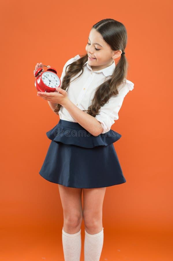 Σχολικός χρόνος Εκπαίδευση παιδιών ( χρόνος να πάει στο σχολείο Ευτυχής υπολογισμός ξυπνητηριών λαβής κοριτσιών για το μεσημεριαν στοκ εικόνες με δικαίωμα ελεύθερης χρήσης