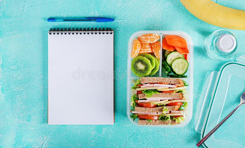 Σχολικό καλαθάκι με φαγητό με το σάντουιτς, τα λαχανικά, το νερό, και τα φρούτα στον πίνακα στοκ εικόνα με δικαίωμα ελεύθερης χρήσης