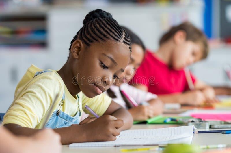 Σχολικό κορίτσι που γράφει στην κατηγορία στοκ φωτογραφία με δικαίωμα ελεύθερης χρήσης