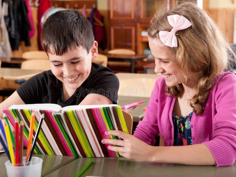 σχολικό χαμόγελο ανάγνωσης κοριτσιών αγοριών βιβλίων στοκ φωτογραφία με δικαίωμα ελεύθερης χρήσης