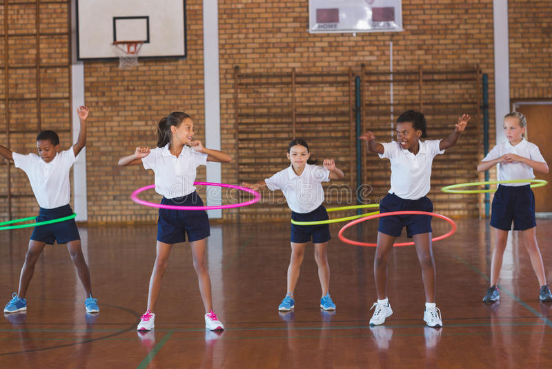 Σχολικά παιδιά που παίζουν με τη στεφάνη hula μέσα στο γήπεδο μπάσκετ στοκ εικόνα με δικαίωμα ελεύθερης χρήσης