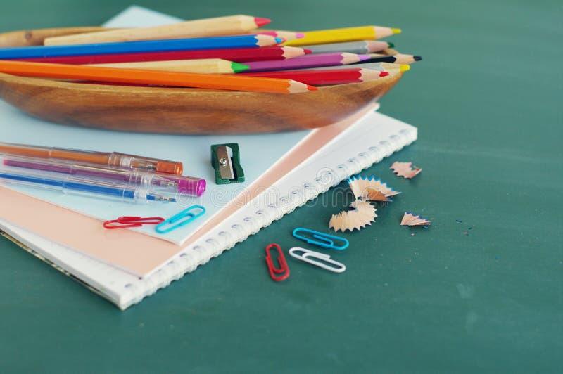 Σχολικές προμήθειες ενάντια σε έναν πράσινο πίνακα στοκ εικόνα με δικαίωμα ελεύθερης χρήσης