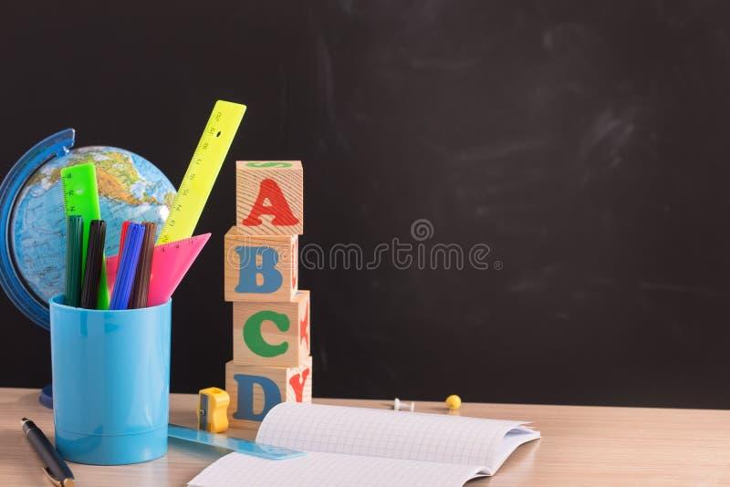 Σχολικές προμήθειες ενάντια στο μαύρο πίνακα στοκ εικόνες με δικαίωμα ελεύθερης χρήσης