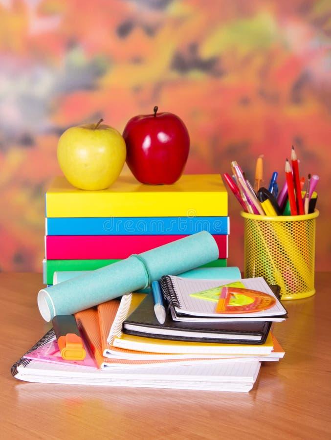 Σχολικές προμήθειες στο υπόβαθρο των φύλλων φθινοπώρου στοκ εικόνες
