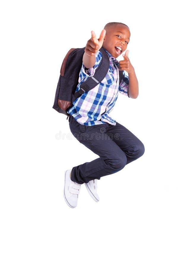 Σχολικό αγόρι αφροαμερικάνων που πηδά και που αποτελεί τους αντίχειρες - ο Μαύρος στοκ εικόνες με δικαίωμα ελεύθερης χρήσης